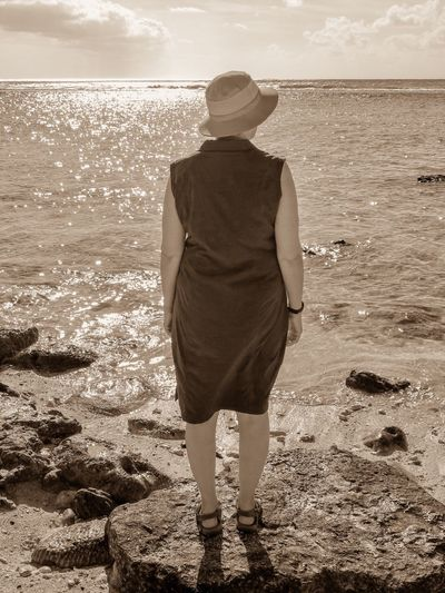Rear view of woman wearing hat standing on rock at beach