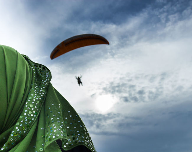 Close-Up Of Woman Looking At Person Paragliding In Sky