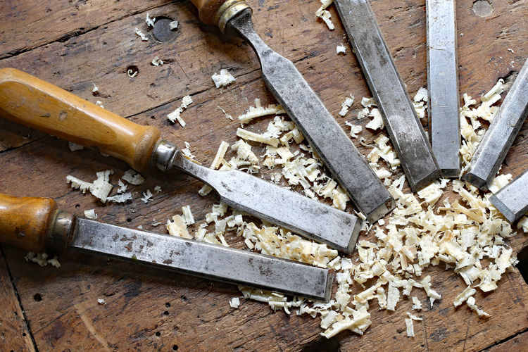 Close-up of chisel and wood shavings on table