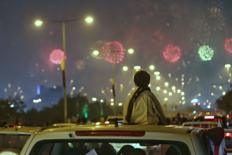Rear view of boy looking at firework display while sitting on car roof at night