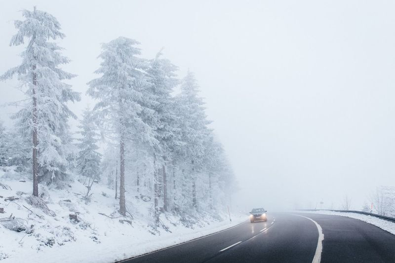 Cars on road against clear sky during winter