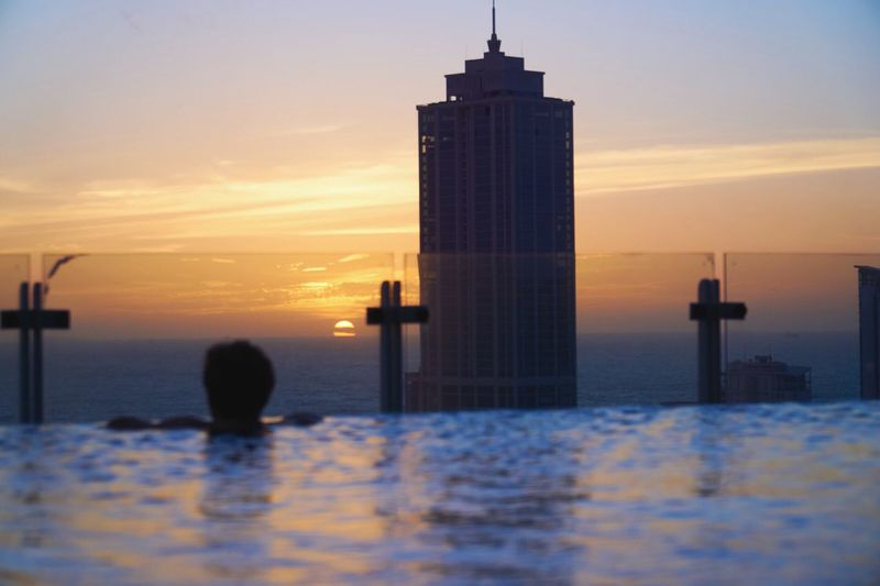 Sunset on the Rooftop of the Cinnemon Red Hotel in Colombo ( Sir Lanka). Pool Water Silhouette Sky Outdoors One Person Skyscraper Beauty In Nature Day Blue City Cloud - Sky Landscape Eyem Holydays Eyemphotography Getting Inspired Mother Nature