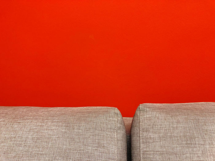Close-up of sofa against orange wall
