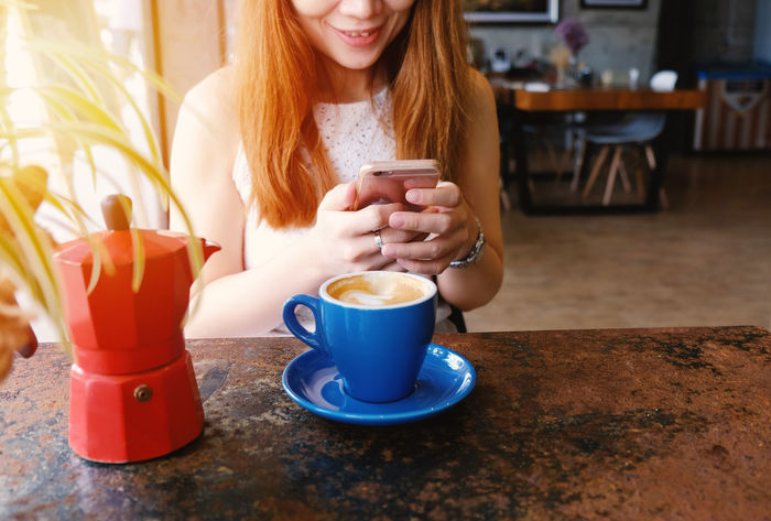 Asian  Cafe Close-up Coffee - Drink Coffee Cup Day Drink Food And Drink Freshness Front View Happy Indoors  Interior Leisure Activity Lifestyles Moka Pot One Person People Refreshment Sitting Smartphone Smiling Table Young Adult Young Women