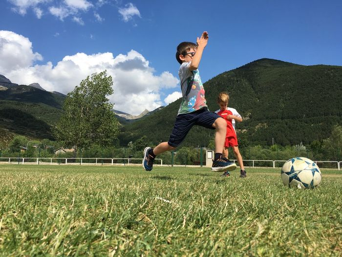 Children playing soccer on grassy field against mountain