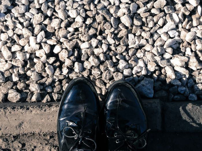 Low section of man wearing shoes standing against stones