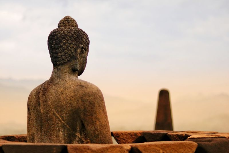 Statue of buddha against sky during sunset