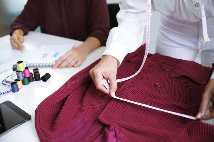 Midsection of fashion designers working in studio