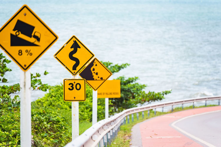 Steep Hill Descent Use Low Gear Traffic Sign on the Road in Thailand Arrow Symbol Communication Day Focus On Foreground Guidance Nature No People Number Outdoors Representation Road Road Sign Sign Symbol Text Transportation Warning Sign Water Yellow