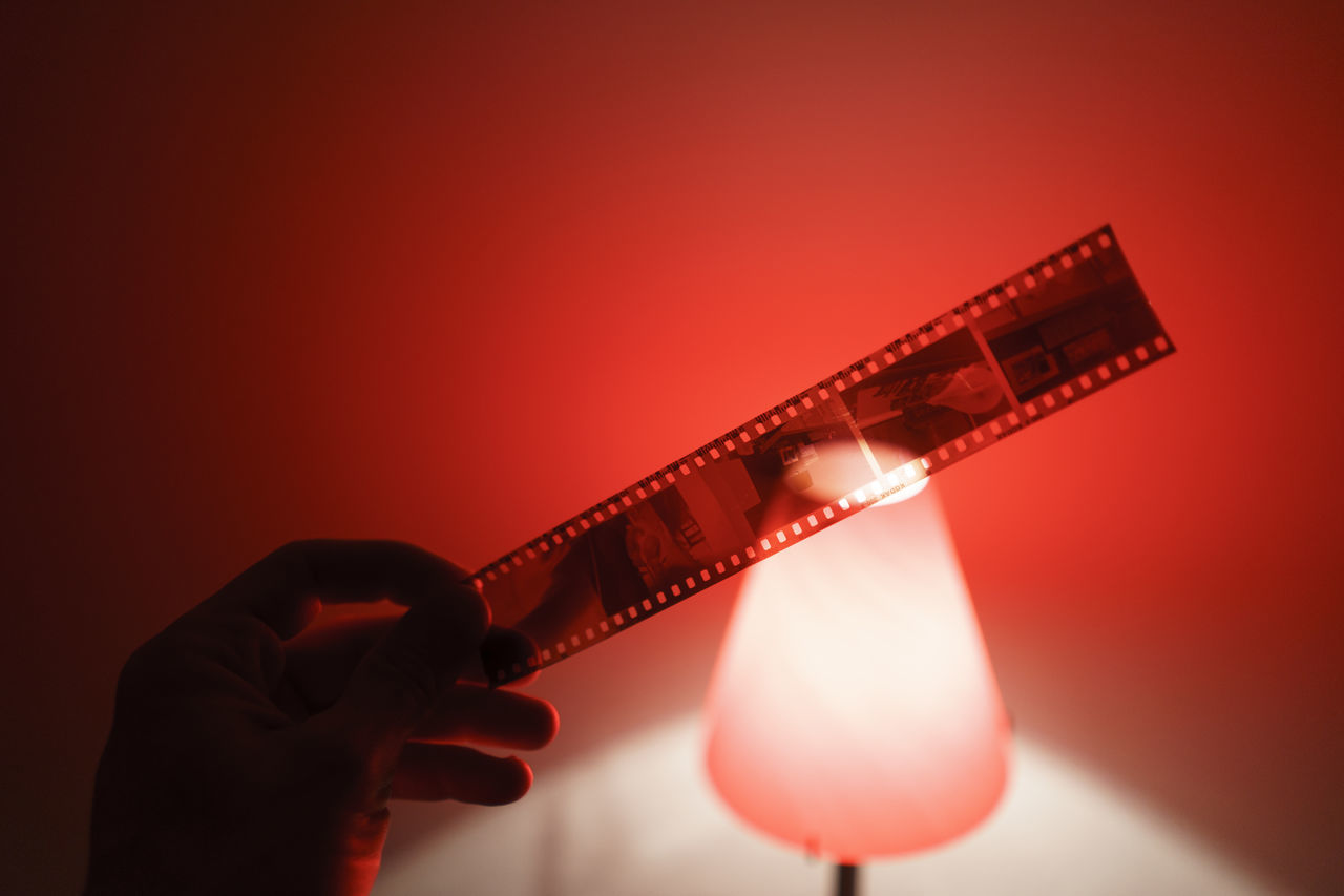 Cropped hand holding film reel by illuminated lamp