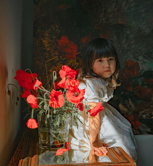 Portrait of girl standing against red wall