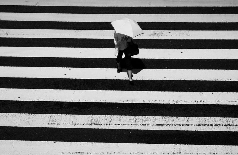 Rear view of woman walking on zebra crossing