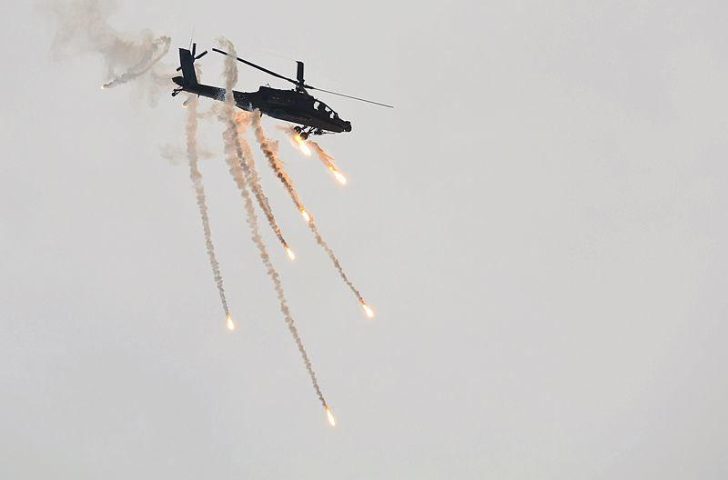 Low angle view of apache helicopter firing missiles against clear sky