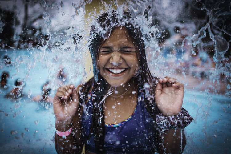 Water splashing on smiling girl in swimming pool