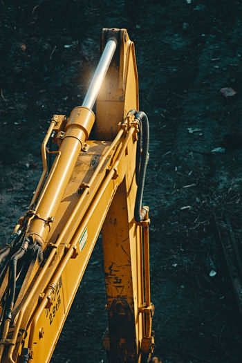 Arm of a yellow excavator in a dark background Excavator Heavy Duty Machine Machinery Machines Mechanic Mechanical Shiny Arm Caterpillar Close-up Cylinder Dark Background Day Digger Hydraulic Machine Part Machinery Close Up No People Outdoors Transportation Yellow