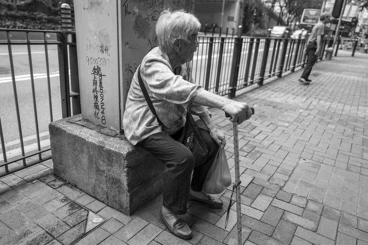 One Person Men Full Length Sitting Casual Clothing Social Issues Senior Adult Street Real People Footpath Males  Adult Day City Architecture Lifestyles Bag Outdoors Paving Stone