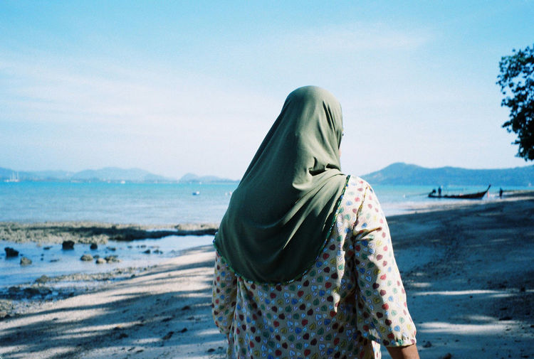 Rear view of woman wearing hijab walking at beach against sky