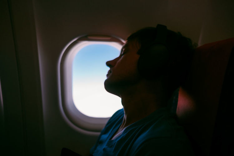 Window Seat Window One Person Transportation Airplane Mode Of Transportation Vehicle Interior Air Vehicle Side View Lifestyles Travel Headshot Leisure Activity Journey Portrait Looking Young Adult Flying Outdoors Contemplation Profile View Headphones Clouds And Sky