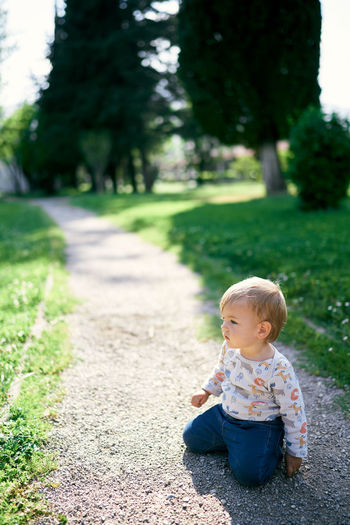 Full length of cute boy sitting on grass