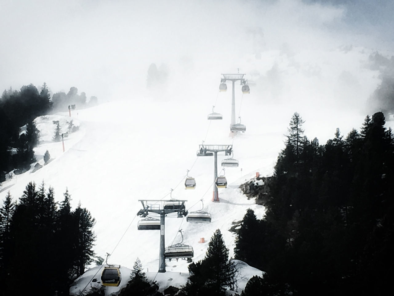 tree, outdoors, winter, nature, snow, mountain, day, cold temperature, fog, no people, sky, transportation, scenics, beauty in nature, architecture, travel destinations, building exterior, ski lift