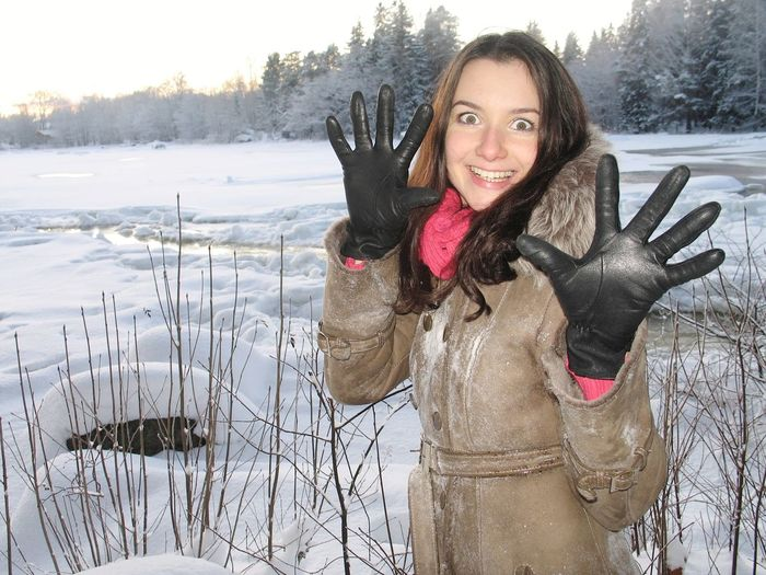 Portrait of smiling young woman gesturing while standing on snow covered field