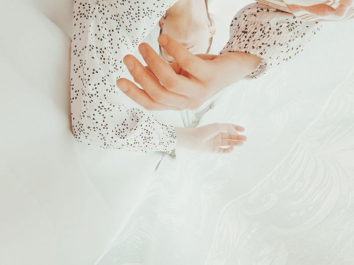 Midsection of woman touching white bed