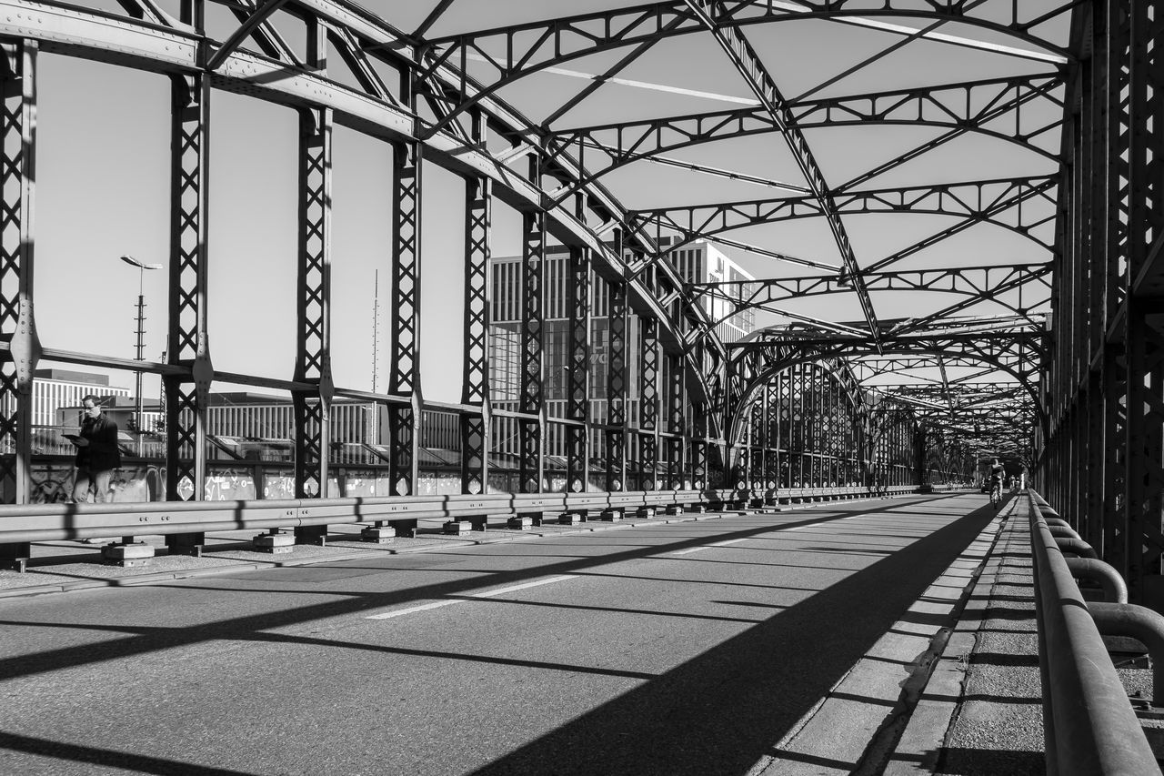 metal, day, bridge - man made structure, transportation, built structure, sunlight, architecture, connection, railroad track, outdoors, rail transportation, sky, cable, clear sky, shadow, no people, city