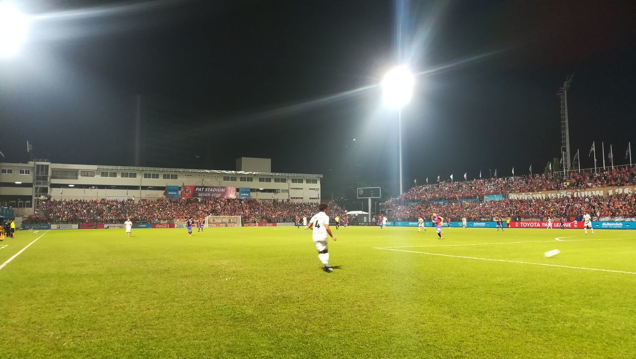 playing, real people, sport, soccer, grass, large group of people, men, night, sportsman, competition, competitive sport, stadium, floodlight, soccer player, soccer field, playing field, togetherness, illuminated, sports team, outdoors, only men, adult, adults only, people