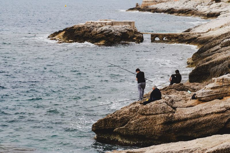 People standing on rock by sea
