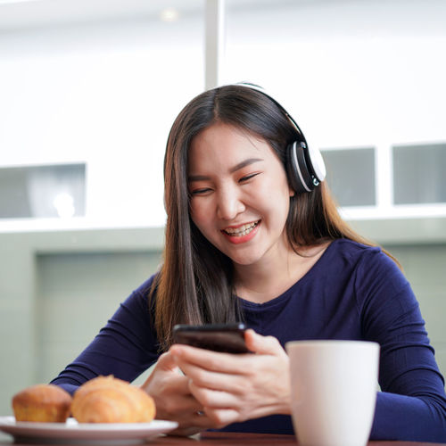 Portrait of smiling woman holding mobile phone