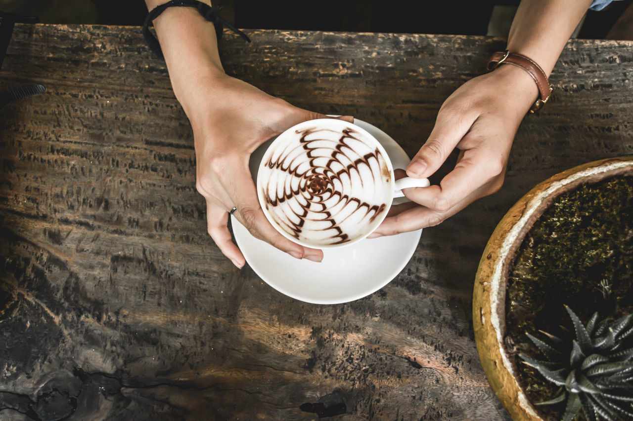 High Angle View Of Hands Holding Hot Chocolate
