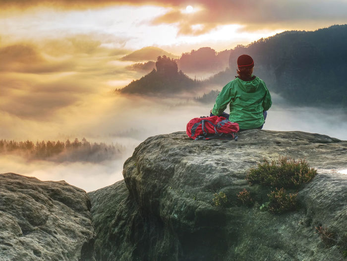 Alone girl sits with her back on a cliff against huge misty mountain