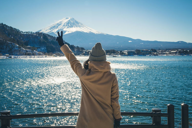 Rear view of woman gesturing peace sign while standing against lake in winter