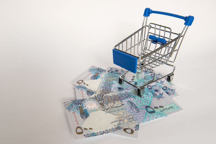 Doha Blue Business Consumerism Copy Space Currency Cut Out Economy Finance Indoors  No People Paper Currency Qatar Retail  Riyal Shopping Shopping Basket Shopping Cart Single Object Studio Shot Wealth Western Script White Background