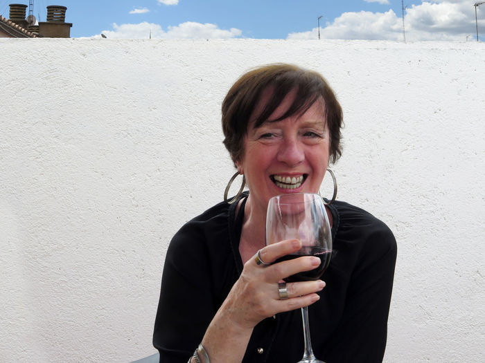 Portrait of smiling woman holding wineglass while sitting on chair against wall