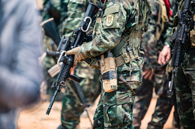 Midsection of army soldiers with rifle