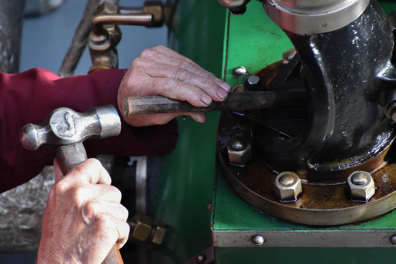 Cropped hands of person holding hand tools on equipment