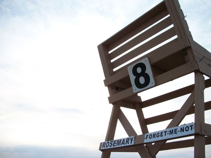Low angle view of number on chair against sky