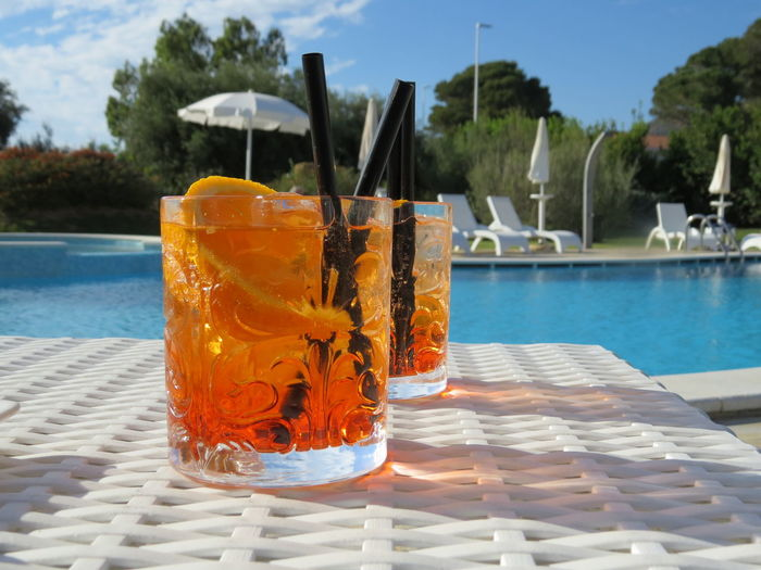 Close-up of drink by swimming pool