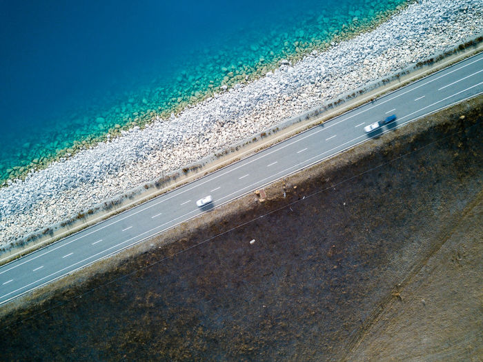 Aerial view of cars on road by sea