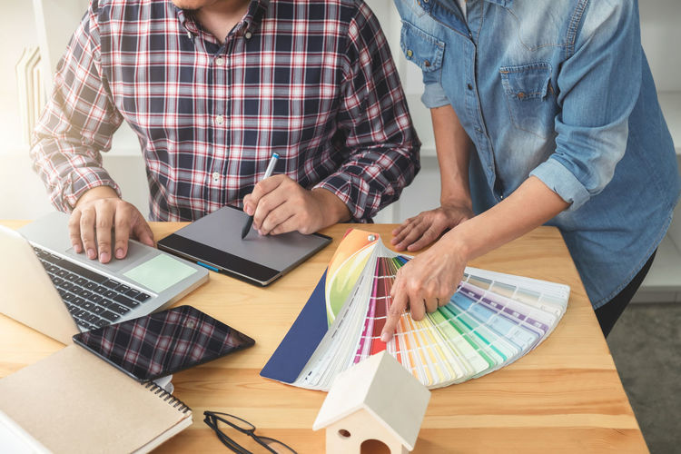 Cropped Image Of Interior Designers Working At Office While Using Graphics Tablet And Laptop