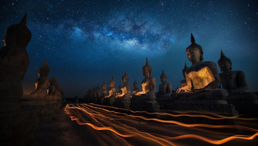 Buddha Statues Under Star Field