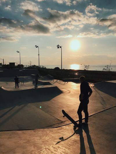Silhouette man at skatepark against sunset