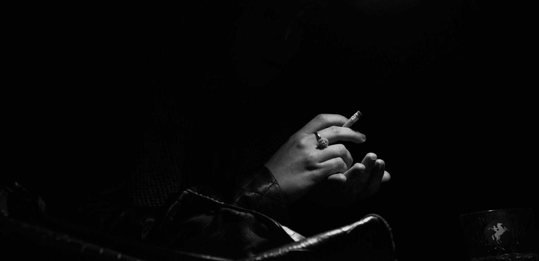 Cropped hands of woman holding cigarette against black background