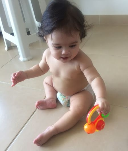 High angle view of shirtless cute baby girl playing with toy on floor at home