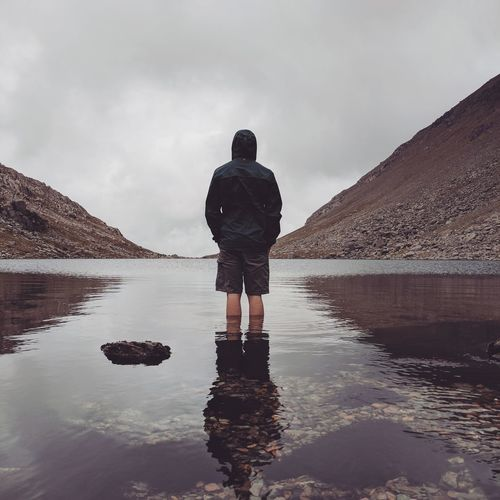 Rear View Of Man Standing On Lake Against Sky