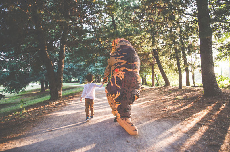 Rear view of boy walking with person wearing dinosaur costume in park