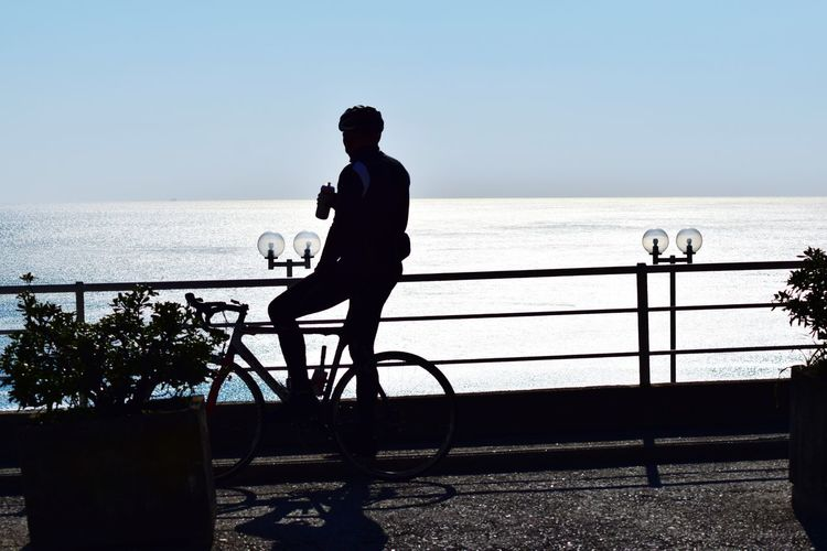 Silhouette Man Riding Bicycle Against Sea