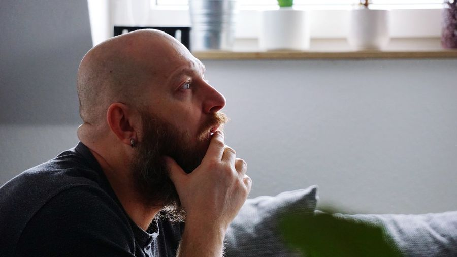Side View Of Bearded Bald Man Looking Away At Home