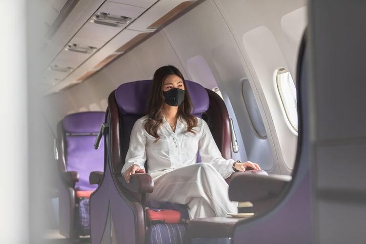 Beautiful woman wearing mask sitting at corporate jet